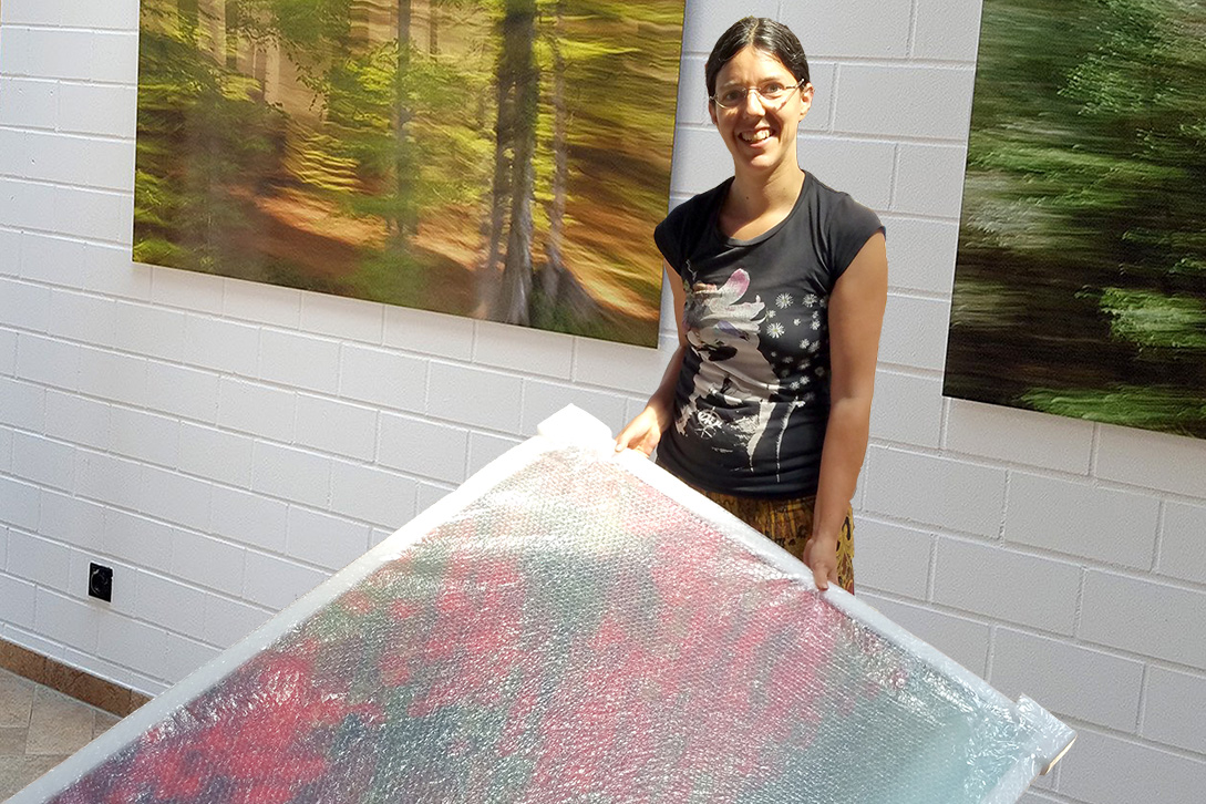 The photo artist Jennifer Scales holding a large photograph in bubble wrap. In the background, other large photographs are already on the wall