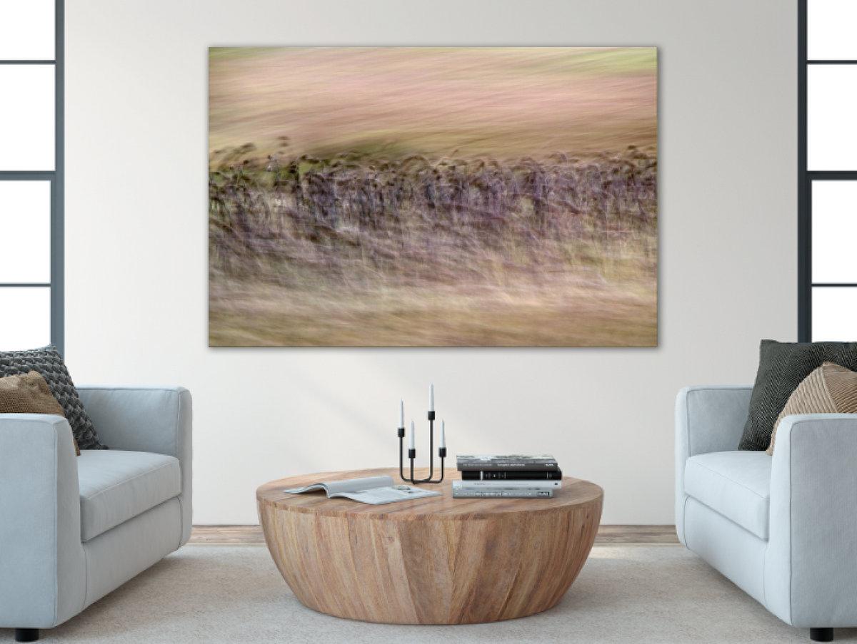 Ein modernenes Wohnzimmer mit einer großen Fotografie an der Wand. Das Motiv ist Natur in Bewegung