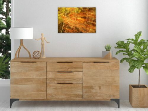 Ein hölzernes Sideboard mit Dekogegenständen unter einer kleinen Fotografie an der Wand. Das Motiv ist Natur in Bewegung