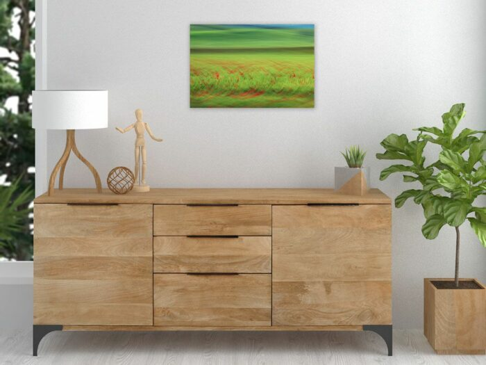 A photograph of landscape in motion above a wooden sideboard