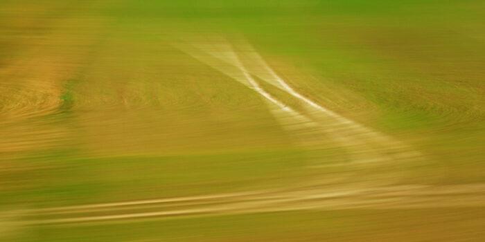 Fotografie in Bewegung, unscharfe Felder in grün und brauntönen mit einer hellen doppelten Fahrspur, die durch die Bewegung zu Strahlen aufgefächert wirkt