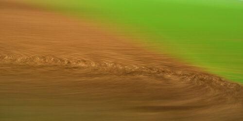abstrakte Forografie, ein braunes Feld und eine grüne Wiese verschmelzen durch starke Bewegungsunschärfe zu abstrakten Flächen