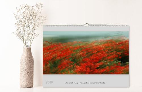 Ein Kalender steht auf einem Sideboard mit Vase und Trockenblumen. Beschriftung: 2019 - Was uns bewegt - Fotografien von Jennifer Scales